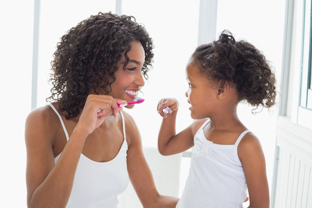 AFRICAN AMERICAN MOTHER AND CHILD BRUSHING TEETH