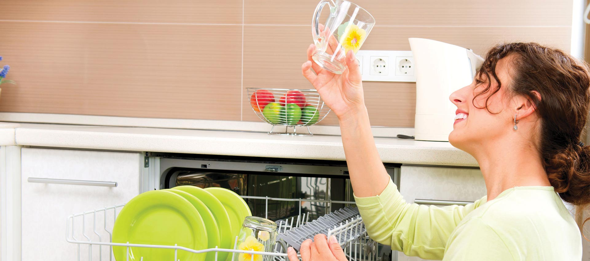 Lady looking at clean glass from dishwasher